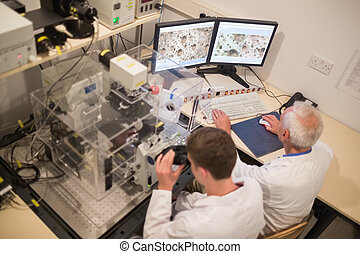 Biochemist and student looking at microscopic images on...