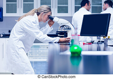 Science student working with microscope in the lab at the...