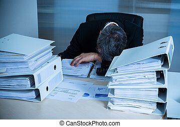 Exhausted Businessman Sleeping At Desk In Office