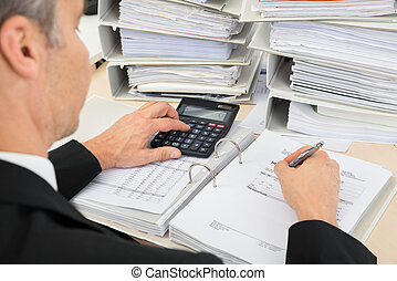 Businessman Calculating Invoices - High Angle View Of...