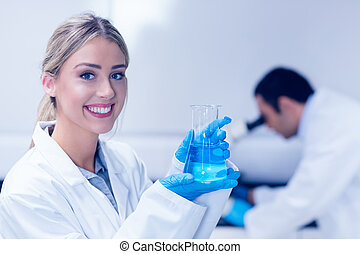 Science student holding blue chemical in beaker at the...