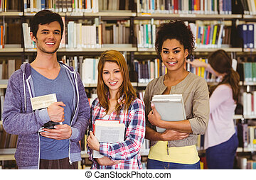 Students standing and smiling at camera holding books in...