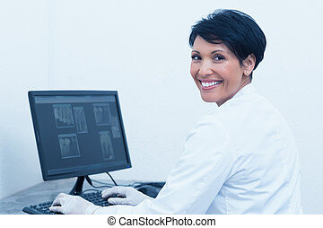 Smiling female dentist with x-ray on computer