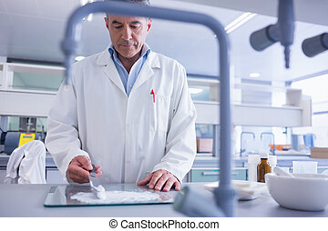 Focused biochemist preparing some medicine in laboratory