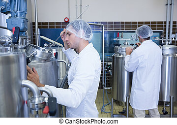 Scientists wearing lab coat and hair net in the factory