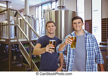 Young men holding a pint of beer smiling at camera in the...