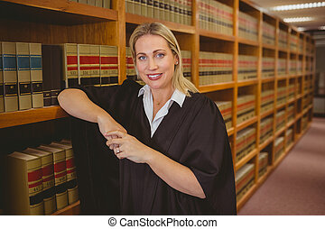 Smiling lawyer leaning on shelf