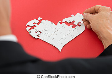 Person Solving Heartshape Jigsaw Puzzle - Close-up Of A...