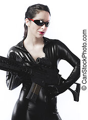 Brunette sexy woman in latex with gun