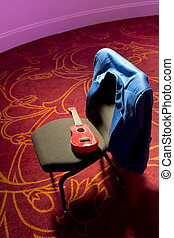 Red Mandolina - A red guitar on a chair in a pink room. Blue...