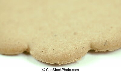 A flat gingerbread on the table. It is brown in color like a...