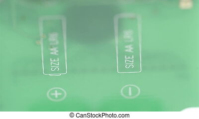 The green micro chip of the battery showing the + - sign of...