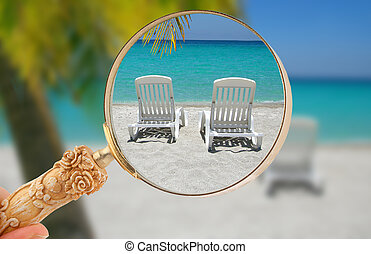 Looking into a Caribbean getaway - Hand holding a magnifying...