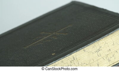 The detail of the bibles cover. It has cross and some...