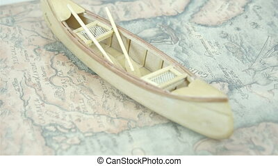 A small wooden canoe boat on top of the map It is white in...