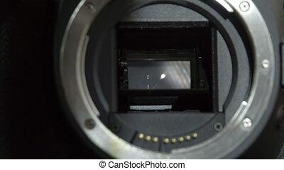 A camera lens opening the shutter - A DSLR camera mirror...