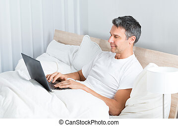 Man Relaxing On Bed Using Laptop - Happy Mature Man Sitting...