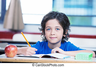 Kid at school writing on his book with an apple on the desk