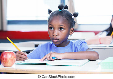 Afro american girl in primary school classroom writing her...