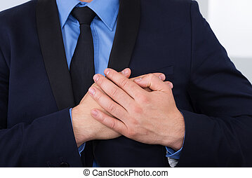 Businessman With Hand On Chest - Close-up Of A Businessman...