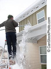 Roof Snow Removal - Caucasian man using rake to shovel heavy...