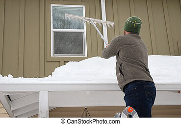 Roof Snow Removal - Caucasian man using rake to shovel heavy...