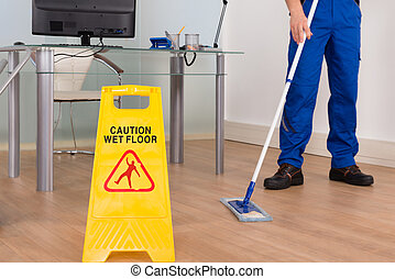 Wet Floor Sign In Office - Close-up Of Janitor Mopping With...