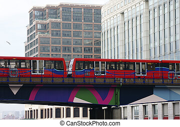 Red Subway - A red subway passes a bridge near on high-rise...