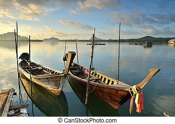 longtail boats - Traditional thai longtail boats at sunset...