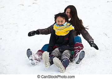 Two sisters sledging holding each other - Girl sledging in...