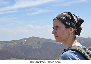 Woman resting on top of a mountain. Hiking and climbing on the trail
