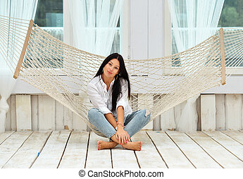 Beautiful smiling young woman relaxing in hammock at home -...
