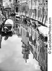 Empty gondolas moored in water canal bw - A view of empty...