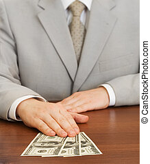 Hand of businessman holding dollars on table