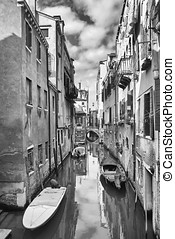 Gondolas parked in water canal bw - A view of empty boats...