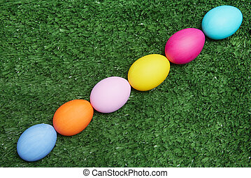 Spring holiday symbols - Line of painted eggs on green grass...