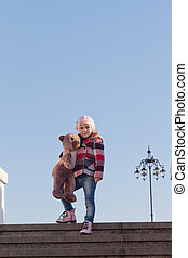 Girl with a big toy bear costs on a ladder