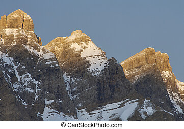 three snow-capped peaks - three snowy peaks at sunrise in...
