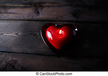 Burning candle - Red heart shaped burning candle on wooden...