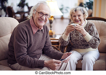 Seniors at weekend - Smiling senior man with touchpad...