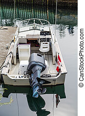 Black Motor on White Boat with Canadian Flag - A small white...