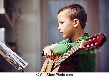 Little guitarist - Little boy is playing the guitar at home