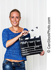 woman with clapperboard - a woman holds a typical clapper in...