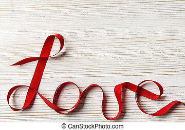 Love Ribbon Word Twisted over White Wooden Background...