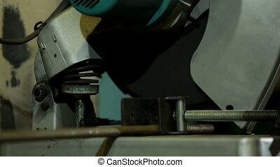 Circular saw closeup - Circular saw cuts metal at a factory...