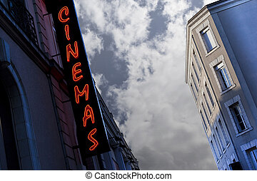 Neon sign of a movie theater at dusk