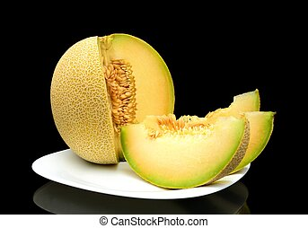 Melon galia with slices on plate isolated black in studio -...