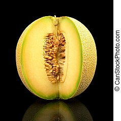 Melon galia notched with seeds isolated black in studio -...