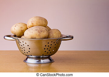 Maris piper potatoes in a colander