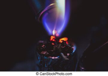 Macro of lighting up a cigarette with marijuana, black background